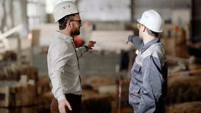 The builder in a protective helmet shows the businessman the scope of work for the near future, the men shake hands and stock video footage