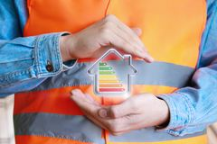 Builder protects the house with a protective gesture of hands. The concept of building energy-efficient houses stock image