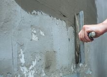 Builder puts mortar trowel wall. Plaster walls. Exterior finish. Carrying out external repair works of the building royalty free stock photography