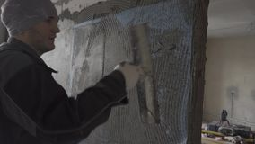 The builder puts on top of the mesh against the background of the second room. Builder in working clothes with a bandana on his head and gloves on his hands stock video footage