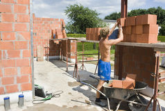 Builder putting bricks on scaffolding Stock Photo