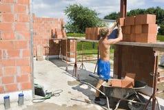 Builder putting bricks on scaffolding. On construction site Stock Photo