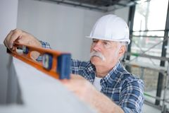 Builder putting spirit level on wall division Stock Image