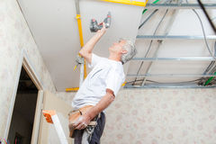Builder putting up suspended ceiling Stock Photo