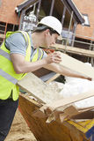 Builder Putting Waste Into Rubbish Skip Stock Photo