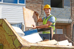 Builder Putting Waste Into Rubbish Skip Stock Image