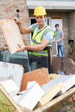 Builder Putting Waste Into Rubbish Skip Royalty Free Stock Photos