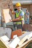 Builder Putting Waste Into Rubbish Skip Stock Photography