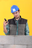 Builder reading a text message Royalty Free Stock Image