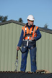 Builder ready to go. A builder wearing a safety harness while working at heights waits for instructions from the foreman Stock Photography