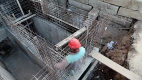 Builder with red hard hat at project site. Building of foundation. Worker at construction site. Unfinished construction. Building of foundation. Builder with red stock footage