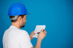 Builder referring to a page of notes Royalty Free Stock Photos
