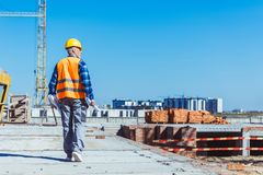 Builder in reflective vest and hardhat walking across a construction site with rolls of plans. In his hands royalty free stock images