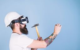 Builder and renovation concept. Man with beard in VR glasses holds hammer, light blue background. Hipster busy with. Renovation in virtual reality. Guy with HMD stock photos
