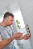 Builder repairing light switch stock photo