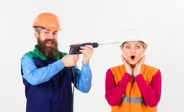 Builder, repairman makes hole in female head. Woman with scared face in helmet, hard hat. Family making repair. Annoying repair concept. Man with happy face stock images