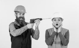 Builder, repairman makes hole in female head. Woman with scared face in helmet, hard hat. Family making repair. Annoying repair concept. Man with happy face royalty free stock photos