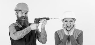 Builder, repairman makes hole in female head. Woman on scared face in helmet, hard hat. Husband annoying his wife. Annoying repair concept. Man with happy face stock image