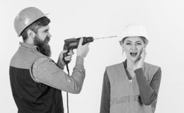 Builder, repairman makes hole in female head. Family making repair. Annoying repair concept. Man with shouting face drills head of woman, white background royalty free stock photos