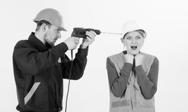 Builder, repairman makes hole in female head. Headache concept. Woman with screaming face in helmet, hard hat. Husband. Annoying his wife. Man with drill tool royalty free stock image