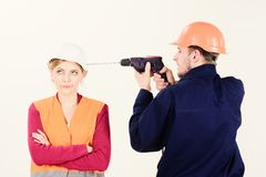 Builder, repairman makes hole in female head. Woman with bored face in helmet ignoring husband annoying her. Marriage issues concept. Man with drill tool royalty free stock photos