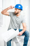 Builder or repairman portrait. Portrait of a handsome builder, foreman or repairman in the helmet sitting with drawings on ladder in the white interior Royalty Free Stock Image