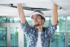 Builder replacing ceiling panel. Young Royalty Free Stock Images