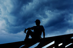 Builder resting on top of roof Royalty Free Stock Photo