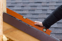 Builder or roofer holding a spirit level Royalty Free Stock Image