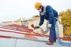 Builder roofer painter worker. Roofer builder worker with pulverizer spraying paint on metal sheet roof Stock Photo