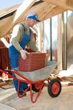 Builder roofer and wheel barrow. Roofer worker working with red clay tiling and wheel barrow royalty free stock photo