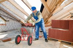 Builder roofer and wheel barrow. Roofer worker loading red clay tiling into wheel barrow for distribution stock image