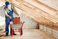 Builder roofer and wheel barrow. Roofer worker loading red clay tiling into wheel barrow for distribution royalty free stock image