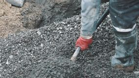 Builder in rubber boots rake macadam with shovel in sewer ditch at building site stock video
