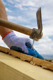 Builder`s hands hammering nail into wood stock image