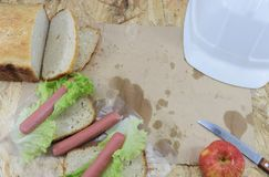 A builder`s lunch, a wooden work table on the construction site with food and tools of the builder. View from above stock image