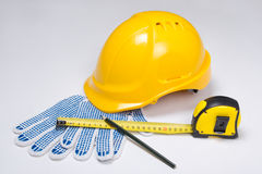 Builder's tools - helmet, work gloves, pen and measure tape  ove Stock Photography