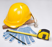 Builder's tools - yellow helmet, work gloves, hammer, pen and me Royalty Free Stock Image