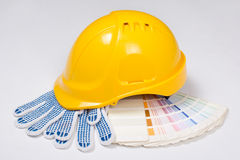 Builder's yellow helmet, work gloves and colorful palette over w Stock Photos
