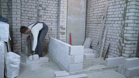 Builder sawing aerated concrete block with hand saw to make it fit the wall gap stock video footage