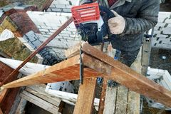 The builder saws on the roof of the chainsaw. Roof rafters. Workers cut the rafters on the roof of the chainsaw house 2019 royalty free stock photos