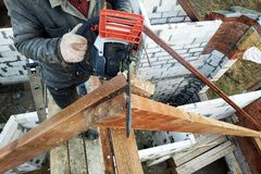 The builder saws on the roof of the chainsaw. Roof rafters. Workers cut the rafters on the roof of the chainsaw house 2019 stock photo