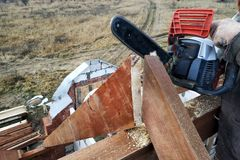 The builder saws on the roof of the chainsaw. Roof rafters royalty free stock image