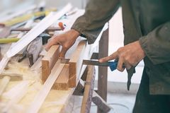 Builder saws a white plastic part. The builder saws a white plastic part Stock Photos