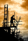 Builder on scaffold building site. Silhouette of construction worker on scaffold Stock Image