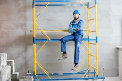Builder on the scaffolding indoors. Builder in blue working uniform sitting on the scaffolding indoors stock images