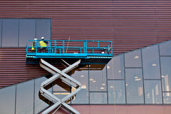Builder on a Scissor Lift Platform at a construction site. Men at work Royalty Free Stock Image