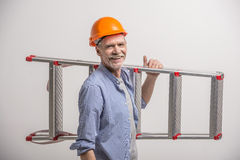 Builder. Senior builder holding stairs on grey background Stock Photography