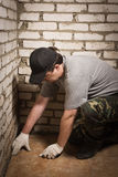 Builder setting tile on cement floor. Stock Photo