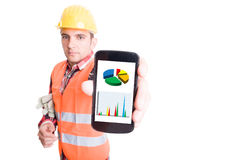 Builder showing smartphone with financial charts Stock Photography